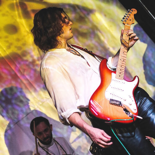 George Pennington playing his strat in a white shirt